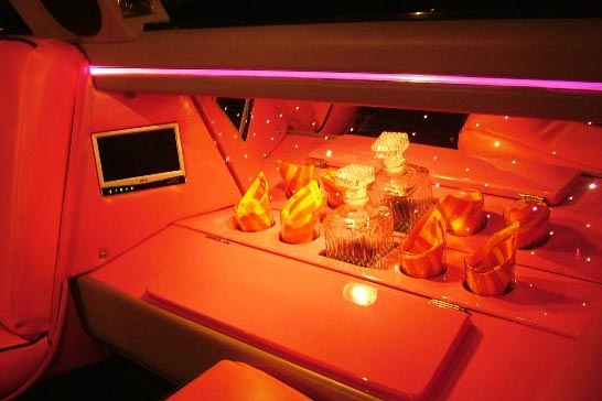 Glassware and monitors inside limousine